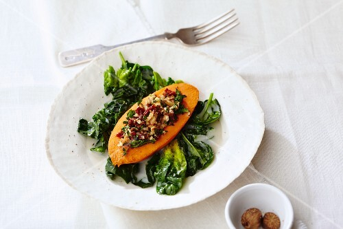 Sweet potato filled with nuts on a bed of coconut spinach