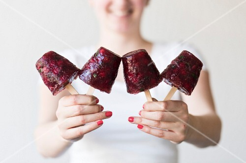 A woman holding redcurrant ice lollies