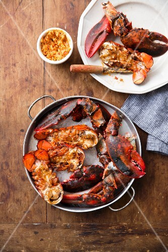 Grilled jointed lobster in a pan and on a plate