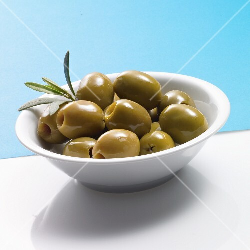 Pitted green olives in a white bowl