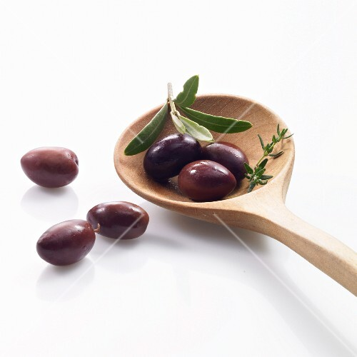 Black olives on a wooden spoon