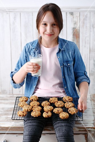 A girl sitting with freshly baked muesli biscuits and a glass of milk