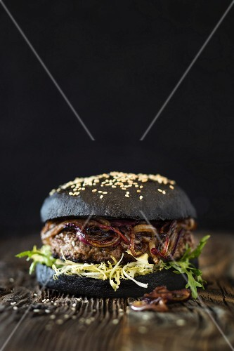 A dry aged hamburger with fried red onions and a black bun