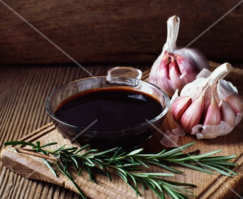 Rosemary, garlic bulbs and a bowl of balsamic vinegar