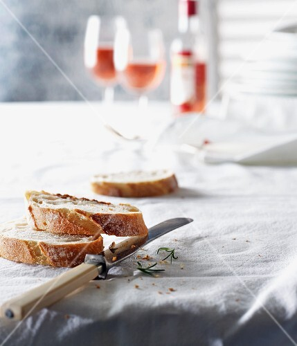 Slices of baguettes with a knife on a laid table