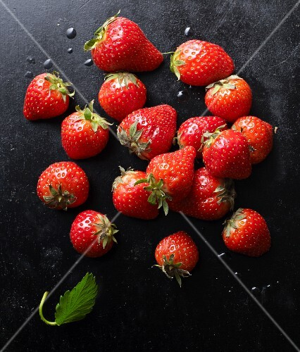 Fresh strawberries with a leaf on a black baking tray