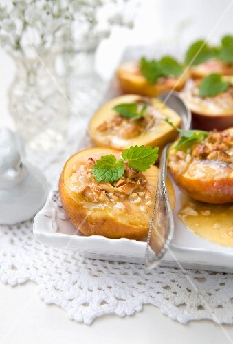 Oven-baked nectarines with honey, nuts and lemon balm
