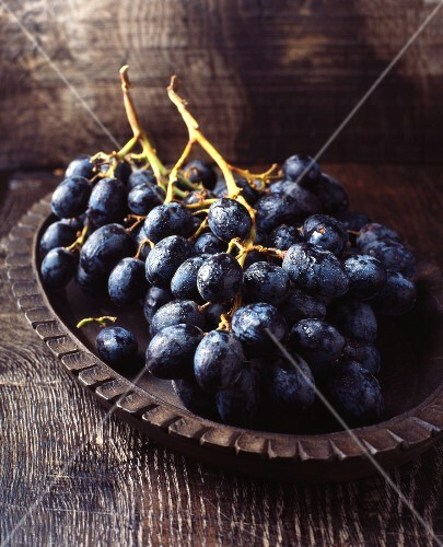 Red grapes in a vintage wooden bowl