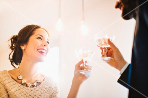 A stylish young couple drinking champagne before a party