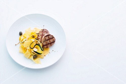 Grilled pork medallions with courgette pasta and lemon and caper butter
