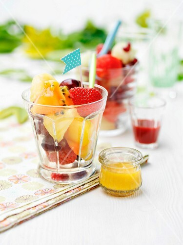 Mixed fruit salad in dessert glasses on a table outside