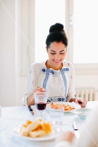 A young woman eating spaghetti at a dining table