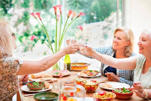 Three older women eating together and toasting with drinks