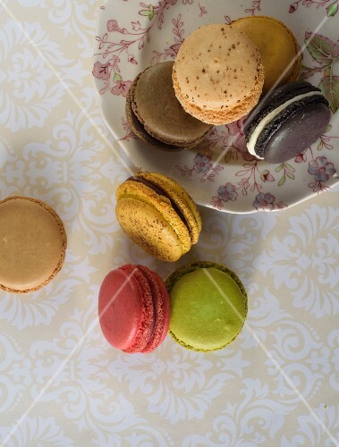 Various macaroons on a plate and on a table (seen from above)