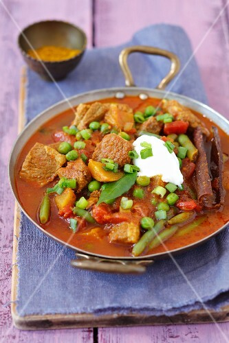 Pork collar curry with tomatoes, mango, green beans, peas and yoghurt