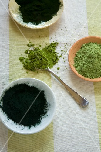 Green superfood powders in bowls and on a spoon
