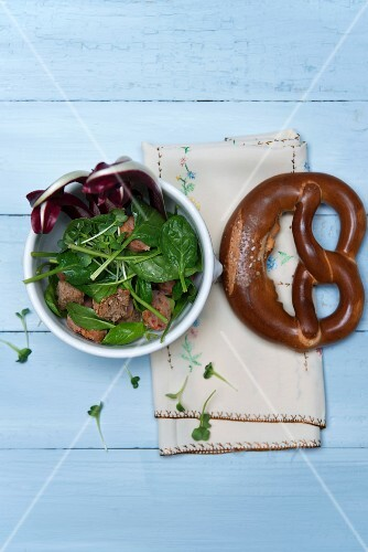 Spinach salad with chorizo, crostini, watercress and Trevisio in a porcelain bowl next to a pretzel