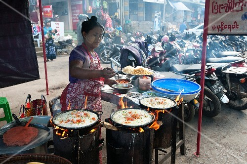 The woman preparing rice pancakes in a street kitchen (Myanmar, Burma)