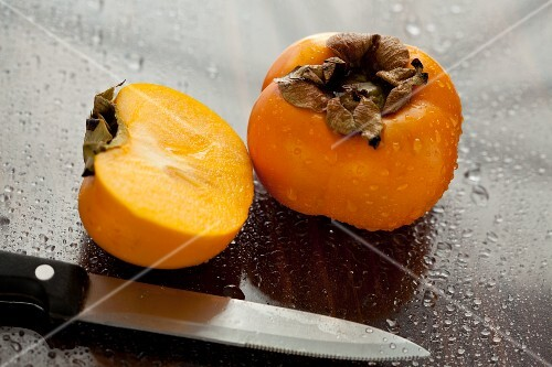Persimmons, whole and halved, sprayed with water drops