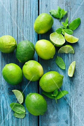 Limes and mint on a blue wooden surface