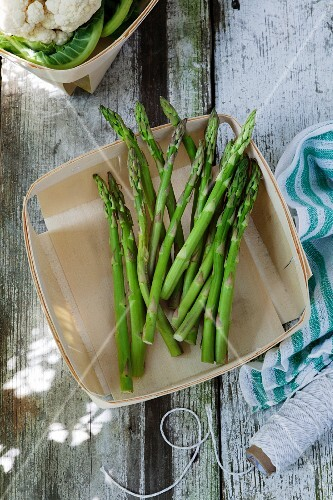 Green asparagus in a wooden basket on a wooden table