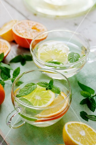 Citrus fruit tea with mint in glass cups