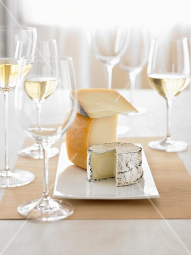 A cheese platter and glasses of white wine