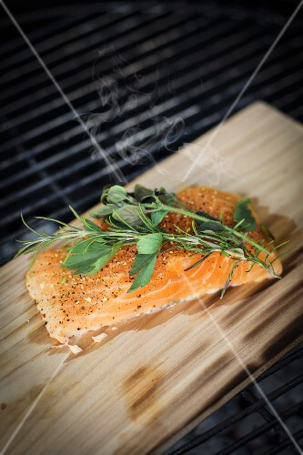 More salmon fed with herbs and spices on smoking board on a grill