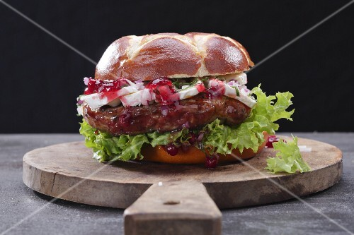A steak burger on a wooden board