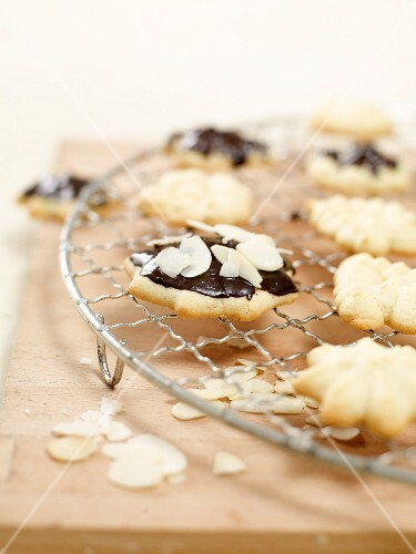 Piped biscuits with almonds and chocolate glaze on a wire rack