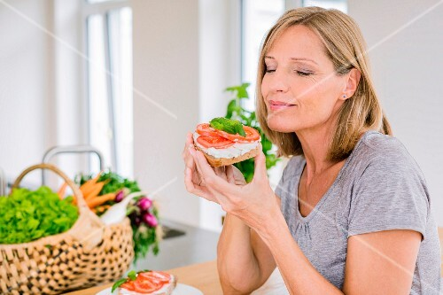 A middle aged woman enjoying an open sandwich with cream cheese and tomatoes