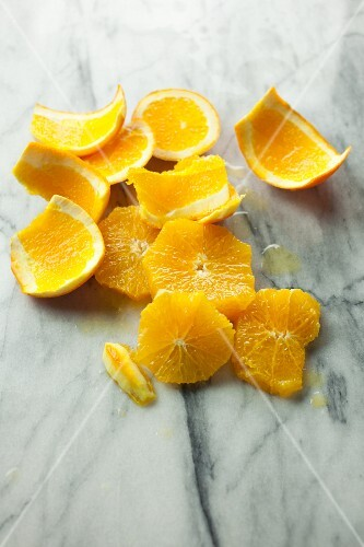 Orange slices and orange zest on a marble table