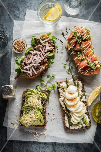 Three open sandwiches with various toppings