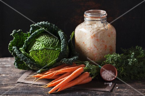 A jar of sauerkraut, savoy cabbage and a bundle of carrots on a rustic wooden table