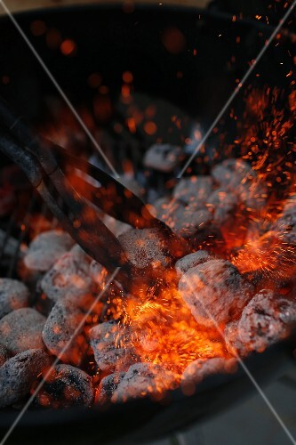 Glowing charcoal being stirred on a barbecue