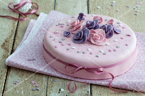 An elegant birthday cake in pink with fondant flowers and a stain ribbon on a rustic wooden table