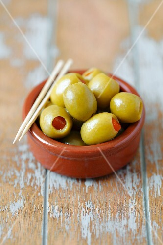 Green olives filled with peppers with toothpicks