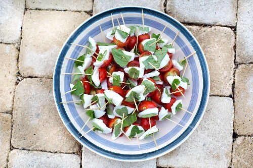 Tomato and mozzarella skewers with basil on a plate