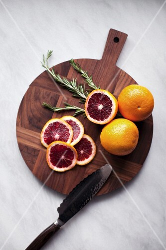 Blood oranges, whole and sliced on a wooden chopping board (seen from above)