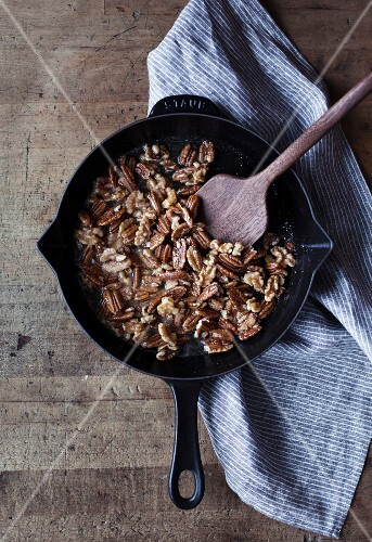 Roasted walnuts and pecan nuts and a pan (seen from above)