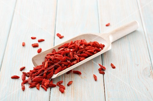 Dried goji berries on a wooden scoop