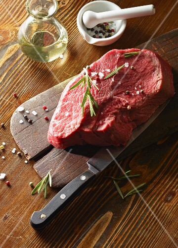 Raw beef fillet (450 g) on a wooden board with rosemary and colourful pepper