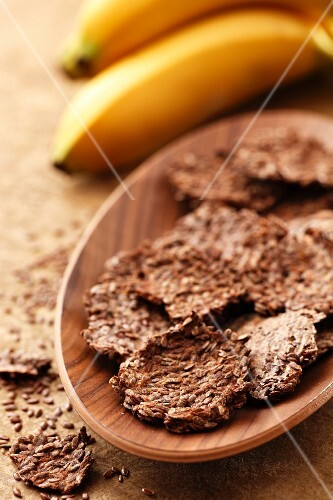 Flax seed and banana biscuits in a wooden bowl with bananas in the background