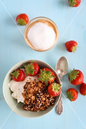 Muesli with strawberries and a cappuccino for breakfast