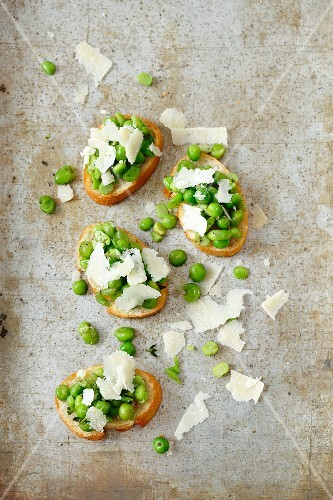 Crostini topped with fresh peas and Parmesan cheese