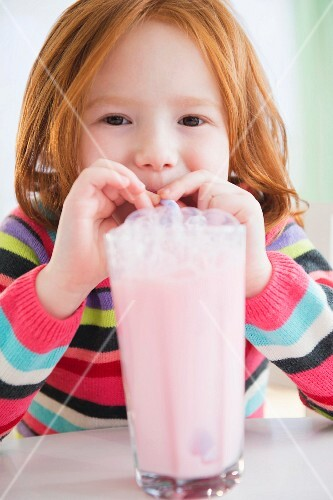A little girl blowing bubbles into her milkshake
