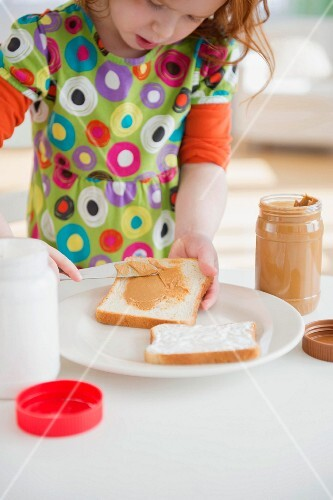A little girl spreading peanut butter onto a slice of bread