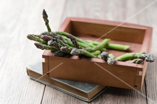 Green asparagus spears in a wooden box