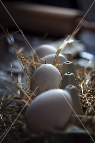 Eggs in an egg box lined with straw
