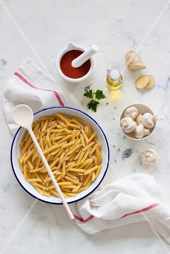 Ingredients for a pasta dish: penne, mushrooms, sieved tomatoes, olive oil and Ginger